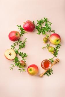 Rosh hashana、パステルピンクのアプリコットテーブルに伝統的なシンボル、リンゴ、蜂蜜、ザクロを使ったユダヤ人の新年の休日のコンセプト。フラットレイ、コピースペースの背景