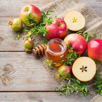 Рош ха-шана, концепция праздника еврейского нового года с традиционными символами, яблоками, медом, гранатом на деревянном деревенском столе. скопируйте космический фон