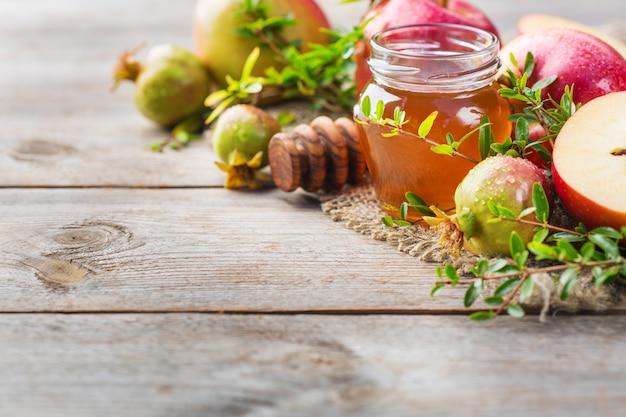 Rosh hashana、伝統的なシンボル、リンゴ、蜂蜜、ザクロを木製の素朴なテーブルに置いたユダヤ人の新年の休日のコンセプト。スペースの背景をコピーする