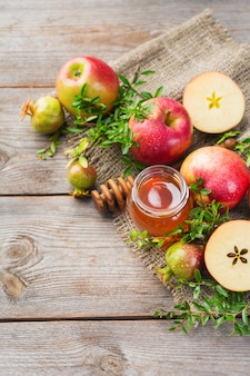 Rosh hashana、伝統的なシンボル、リンゴ、蜂蜜、ザクロを木製の素朴なテーブルに置いたユダヤ人の新年の休日のコンセプト。コピースペース、フラットレイの背景