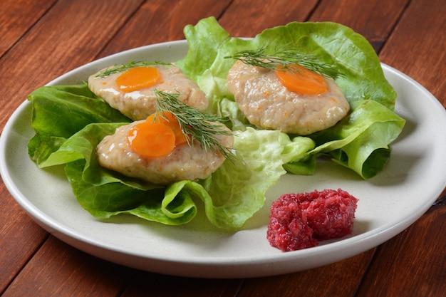Сервировка стола рош ха-шана. традиционная еврейская пасхальная еда - фаршированная рыба с морковью, салатом и хреном.
