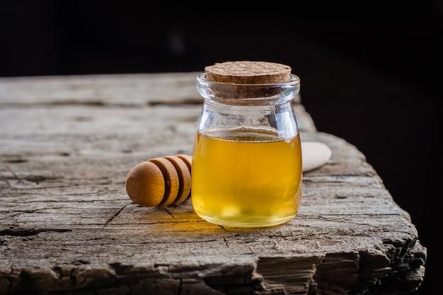 古い木製のテーブル背景に蜂蜜の瓶。ユダヤ人の休日rosh hashanah concept。コピースペース