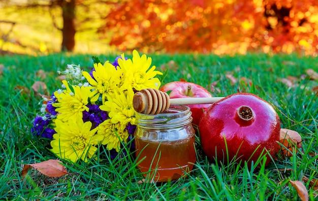 Rosh hashanah jewesh holiday concept - honey, apple and pomegranate traditional symbols.