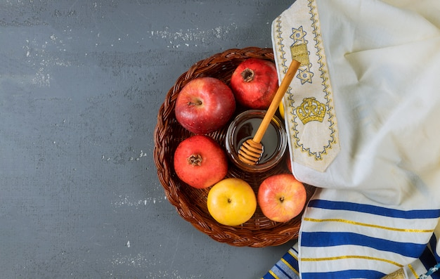 Rosh hashanah jewesh holiday concept - shofar, honey, apple and pomegranate over wooden table.