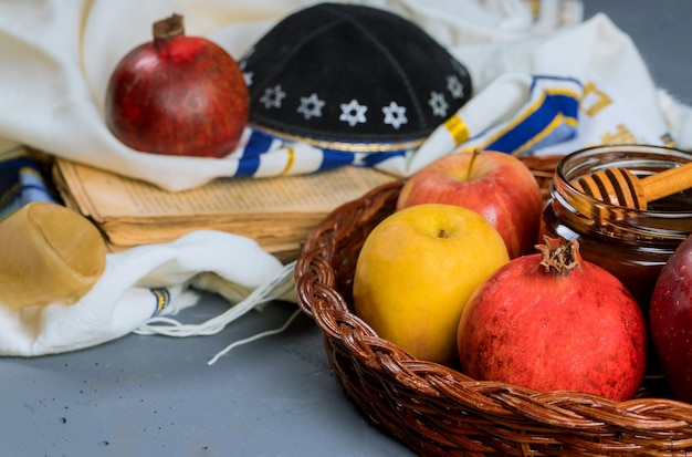 Rosh hashanah jewesh holiday concept - shofar, torah book, honey, apple and pomegranate over wooden table. a kippah a yamolka