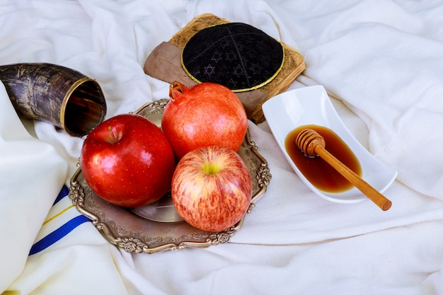 Rosh hashanah jewesh holiday concept - shofar, torah book, honey, apple and pomegranate