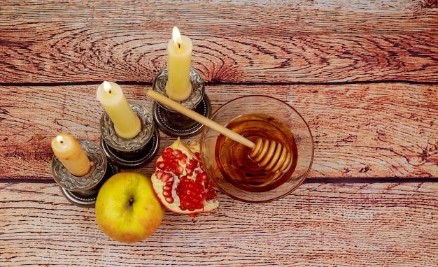 Рош ха-шана еврейская концепция праздника книга торы, мед, яблоко и гранат над деревянным столом. традиционные праздничные символы.