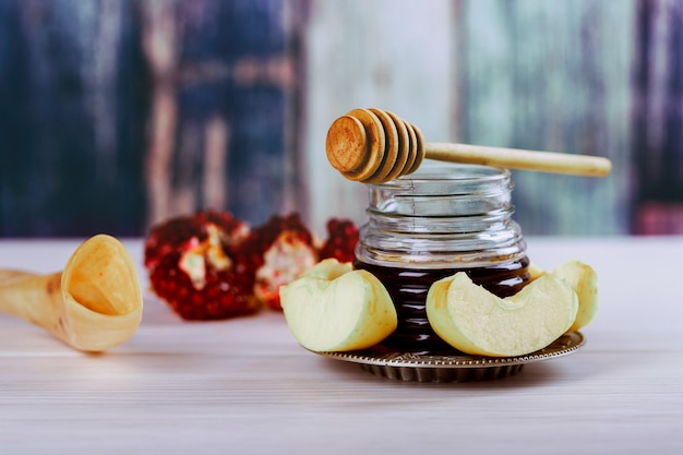 Rosh hashanah jewish holiday concept - shofar, torah book, honey, apple and pomegranate