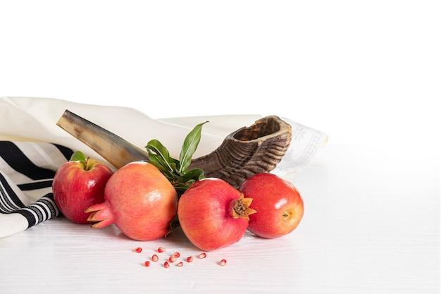Концепция рош ха-шана (еврейский праздник). таллит, шофар (рог), яблоко и гранат, изолированные на белом. традиционный символ праздника.