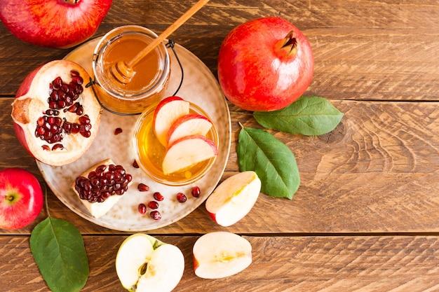 Концепция празднования еврейского нового года в рош ха-шана. мед, гранат и яблоки на деревянном фоне. вид сверху.