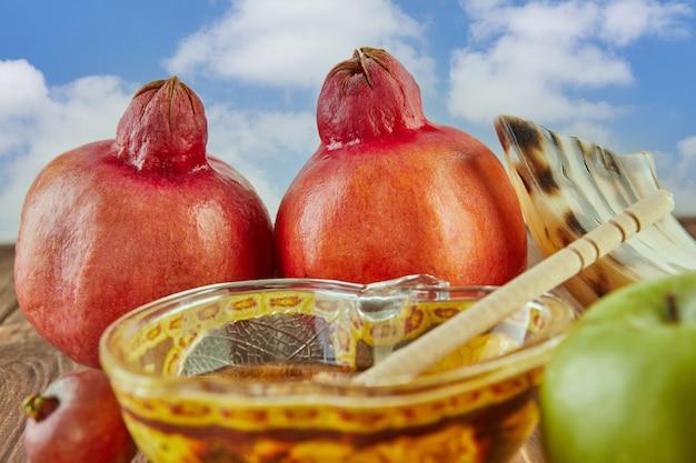 Рош ха-шана - концепция праздника еврейского нового года. чаша в виде яблока с медом, гранатом, шофаром - традиционными символами праздника на фоне неба.