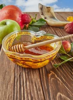 Roshhashanah-ユダヤ人の新年の休日の概念。蜂蜜、ザクロ、ショファーが入ったリンゴの形をしたボウル-空を背景にした休日の伝統的なシンボル。