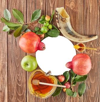 Roshhashanah-ユダヤ人の新年の休日のコンセプト。蜂蜜、ザクロ、ショファーが入ったリンゴの形をしたボウルは、休日の伝統的なシンボルです。フラットレイ。コピースペース