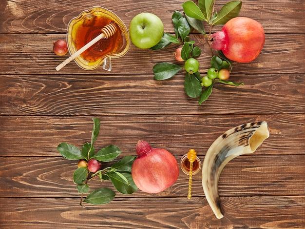 Roshhashanah-ユダヤ人の新年の休日の概念。蜂蜜、ザクロ、ショファーが入ったリンゴの形をしたボウルは、休日の伝統的なシンボルです。フラットレイ。コピースペース