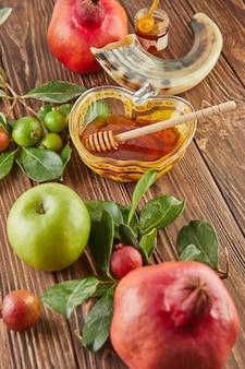 Roshhashanah-ユダヤ人の新年の休日のコンセプト。蜂蜜、ザクロ、ショファーが入ったリンゴの形をしたボウルは、休日の伝統的なシンボルです