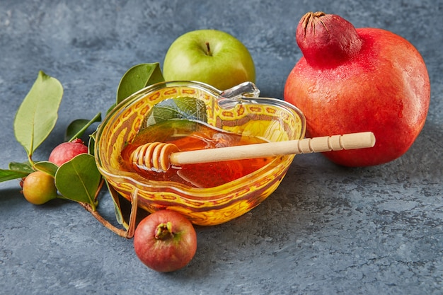 Roshhashanah-ユダヤ人の新年の休日の概念。蜂蜜、ザクロ、ショファーが入ったリンゴの形をしたボウルは、休日の伝統的なシンボルです。