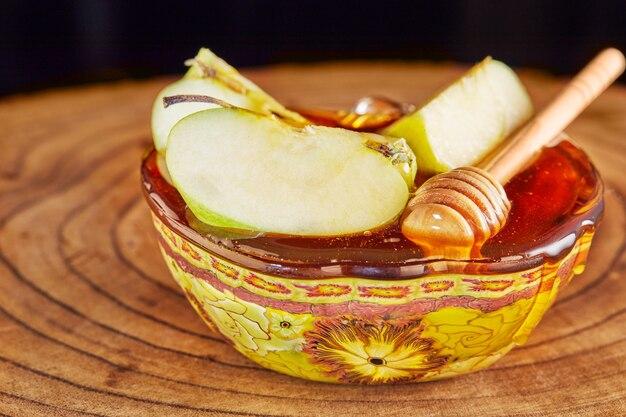 謹賀新年-ユダヤ人の新年休日のコンセプト。蜂蜜と木製のスタンドにスライスしたリンゴをボウルします。