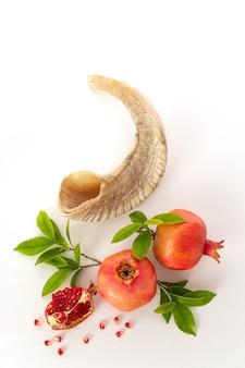 Rosh hashanah (jewish new year holiday) concept -  shofar (horn) and pomegranate on white background. traditional symbols