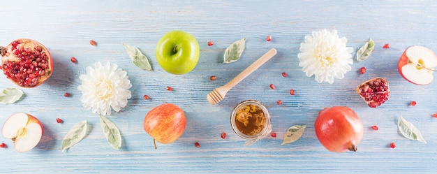 Rosh hashanah (jewish new year holiday), concept of traditional or religion symbols on pastel blue wooden background.
