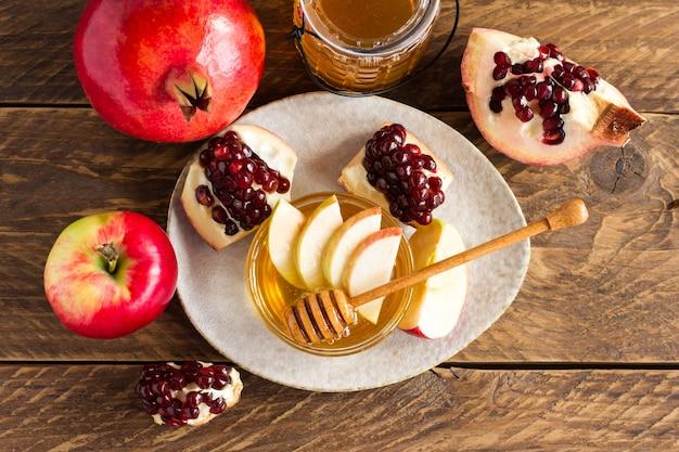 Концепция праздника еврейского нового года рош ха-шана. традиционный символ. яблоки, мед, гранат. на деревянном столе