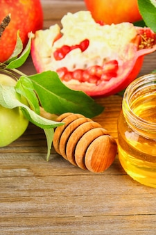 Rosh hashanah jewish new year holiday concept. traditional symbol. apples, honey, pomegranate.