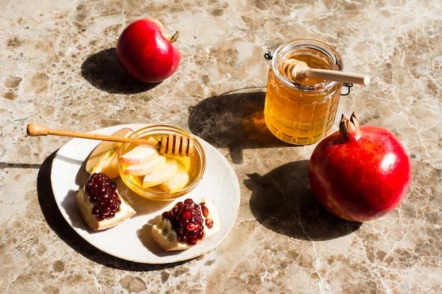 Roshhashanah-ユダヤ人の新年の休日のコンセプト。伝統的なシンボル:大理石の背景にザクロと蜂蜜の瓶と新鮮なリンゴ。