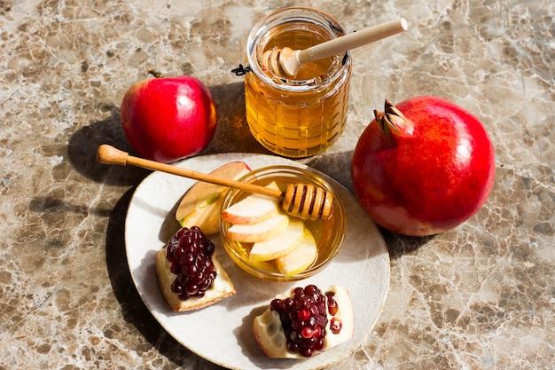 Roshhashanah-ユダヤ人の新年の休日のコンセプト。伝統的なシンボル:大理石の背景にザクロと蜂蜜の瓶と新鮮なリンゴ。上から見る