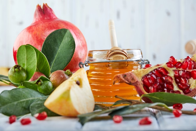 Rosh hashanah -traditional symbols: honey jar and fresh apples with pomegranate on white wooden.