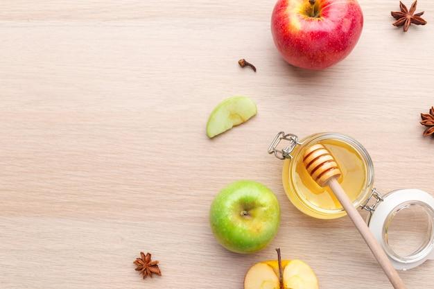 ユダヤ人の休日rosh hashanah蜂蜜と木製のテーブルの上のリンゴ。
