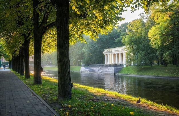 Павильон росси на берегу реки мойки в санкт-петербурге в лучах утреннего солнца и освещенных аллеях деревьев.