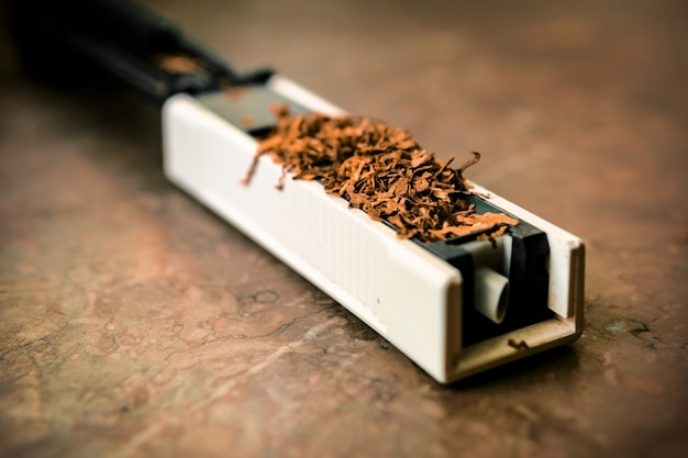 タバコにタバコを詰める機械。空の吐息。テーブルの上のrossypanyタバコ。自家製たばこの生産