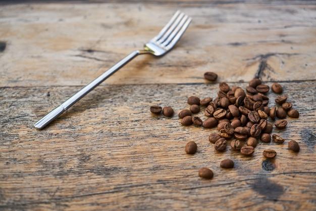 Rosted coffee beans and fork on a table