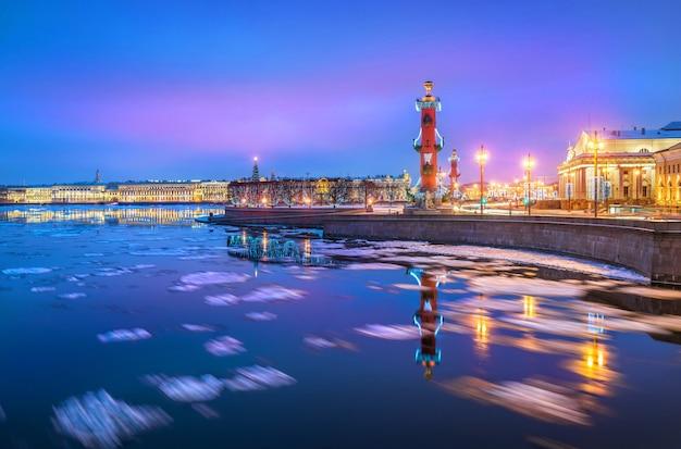 Ростральные колонны на стрелке васильевского острова с отражением в неве в санкт-петербурге зимним синим утром