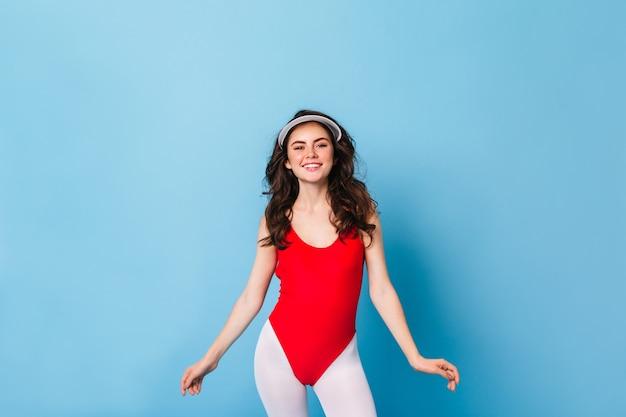 빨간색 바디 슈트와 미소가있는 스포츠 레깅스에 장미 빛 뺨을 입은 젊은 여성이 파란색 벽에 정면으로 보입니다.