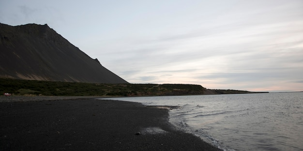 Rosy cloud atmosphere, volcanic mountain next to seashore and gentle waves