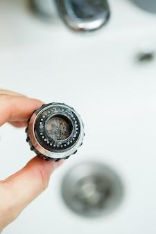 믹서의 회전 노즐로 물의 흐름을 조정합니다. 손을 씻을 수 있는 흰색 세면대