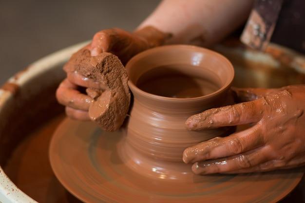 Вращающийся гончарный круг и гончарные изделия на нем вид сверху керамист делает горшок на гончарном круге