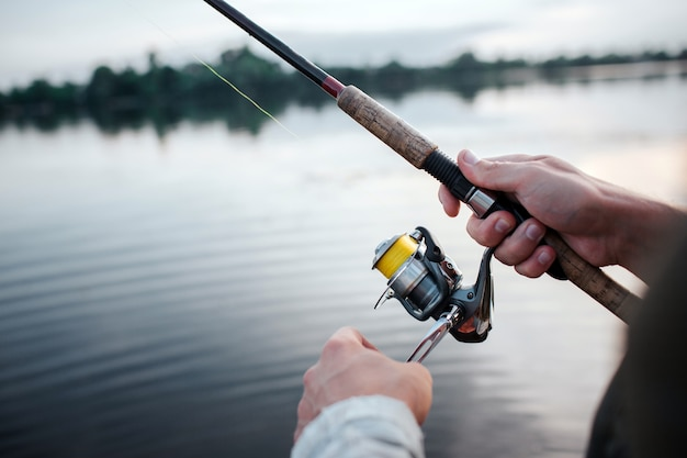 Rotative spinner that guy holds in hands. he rotates reel with left hand. he is at lake. it is evening outside.