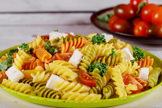Rotini pasta and cherry tomato with green salad on wooden table