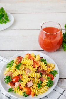 Rotini pasta, ham and vegetables with glass of tomato juice. balanced meal