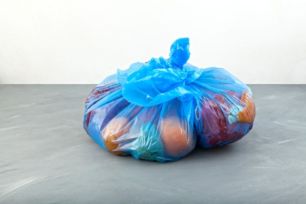 Rotten fruits in blue garbage bag organic food waste imperfect storage vegetables and fruits