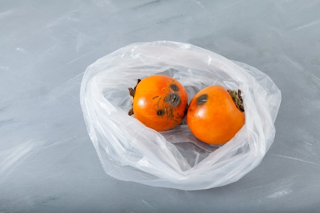 Rotten spoiled persimmon in disposable plastic bag. concept - reduction of organic waste.