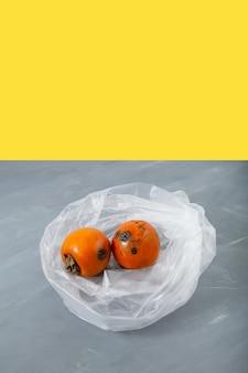 Rotten spoiled persimmon fruit in disposable plastic bag.
