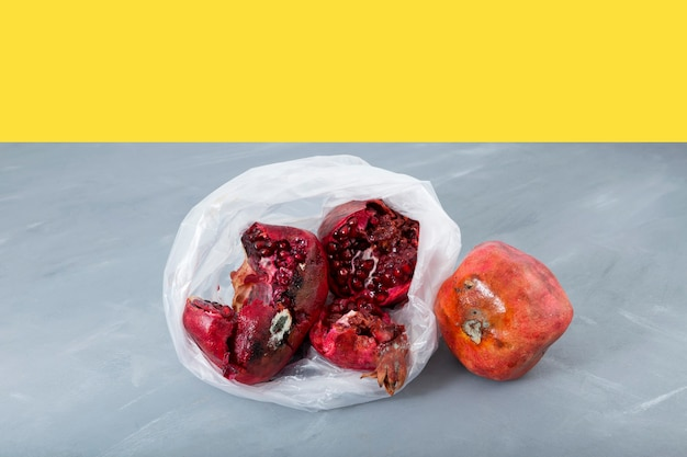 Rotten spoiled pomegranate fruit with mold in disposable plastic bag on yellow-gray