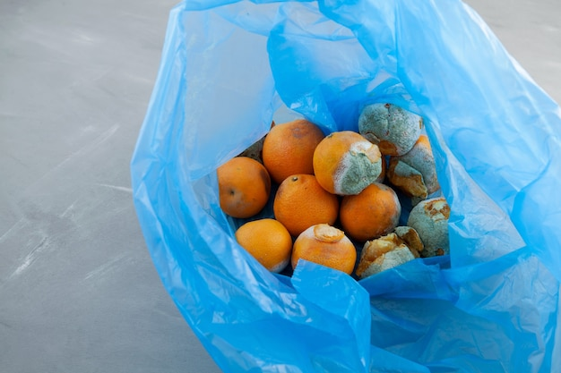腐った甘やかされて育ったみかんまたはみかんの果物をビニール袋に入れて