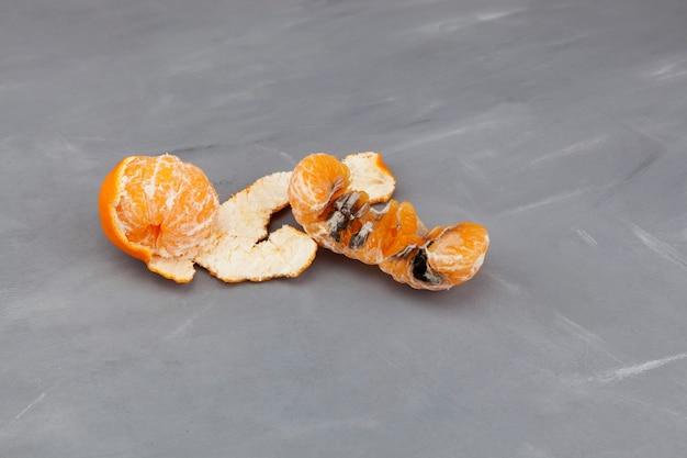 회색 배경에 썩은 버릇없는 귤 또는 만다린. 못생긴 곰팡이가 핀 과일.
