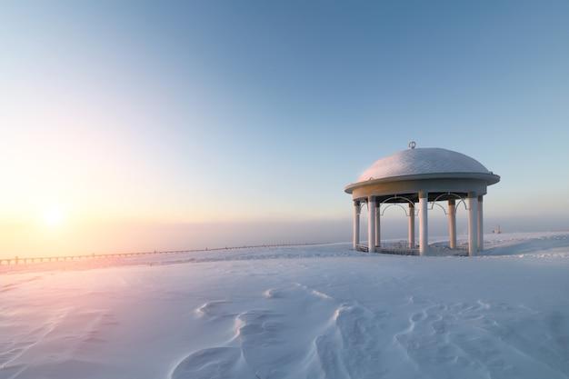 Ротонда на заснеженной равнине. зимний рассвет.