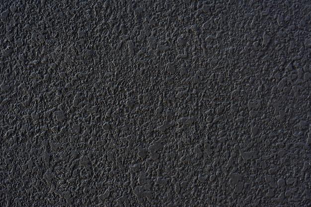 Struttura della parete intonacata di cemento nero grezzo