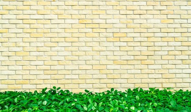 Грубую кирпичную стену украшают зелеными листьями внизу