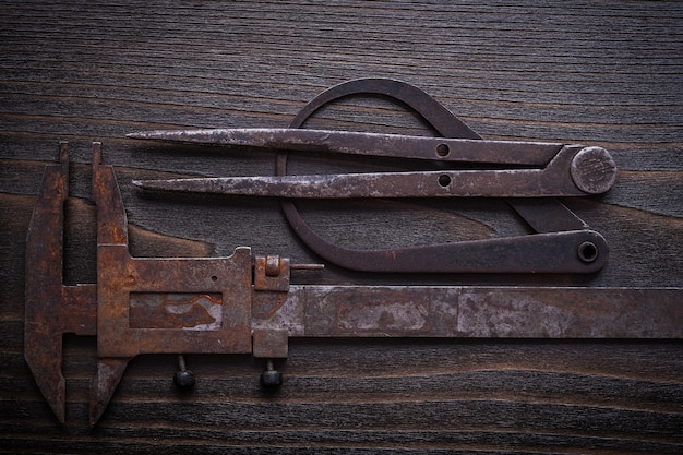 Rough calipers on vintage wood background construction concept